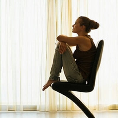 woman sitting on chair knee bent