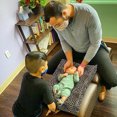 Dr Joe adjusting infant brother overlooking adjustment