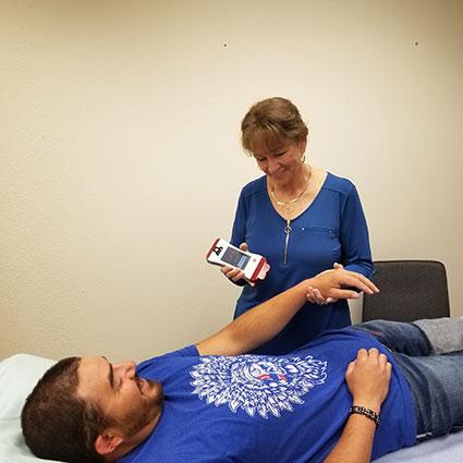 Dr. Jinger doing laser on man's arm