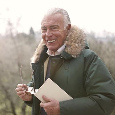 older man smiling wearing winter coat