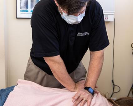 Doctor adjusting woman back