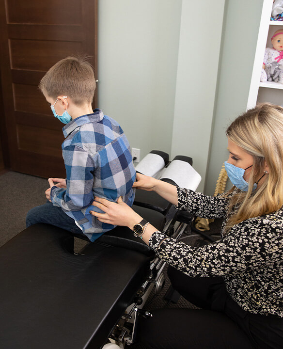 Dr. Annie adjusting young boy