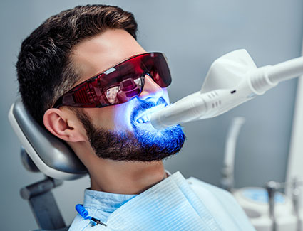 Man getting teeth whitened in office