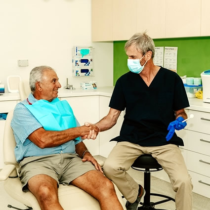 Dentist shaking mans hand