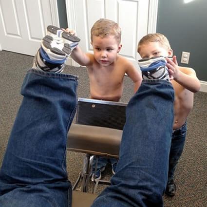 Kids holding man's feet