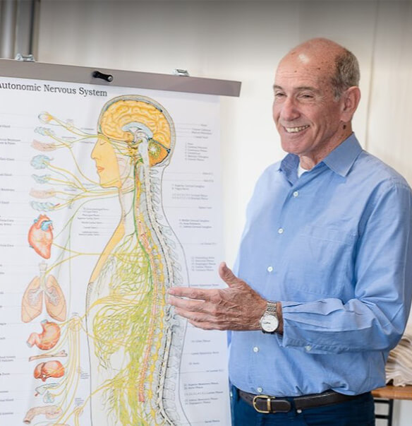 Dr Barry standing by spine picture