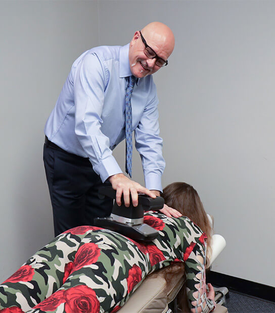 Dr. Smith using adjusting tool on woman's back