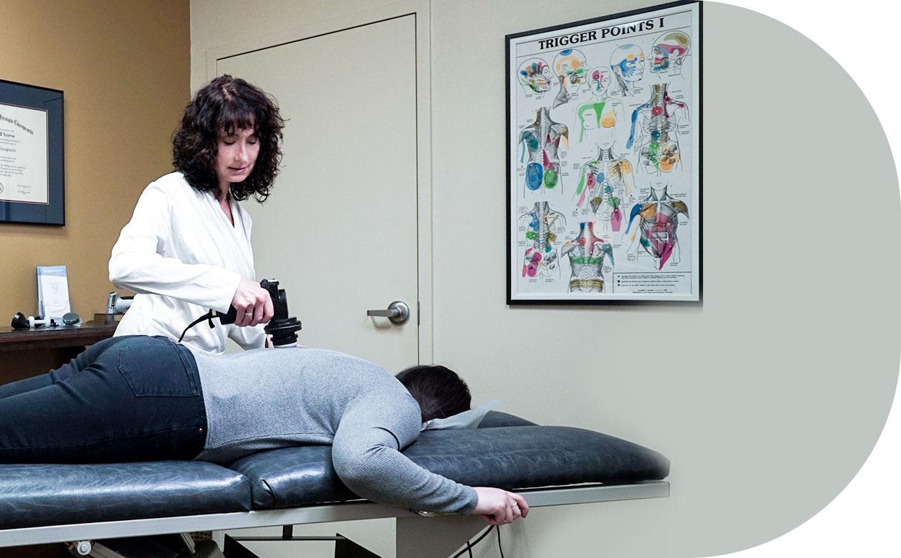 Dr. D'Acierno using tool to adjust back