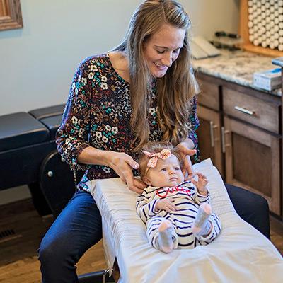 Dr. Erin adjusting a baby
