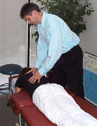 Dr. V checking a patient's back.