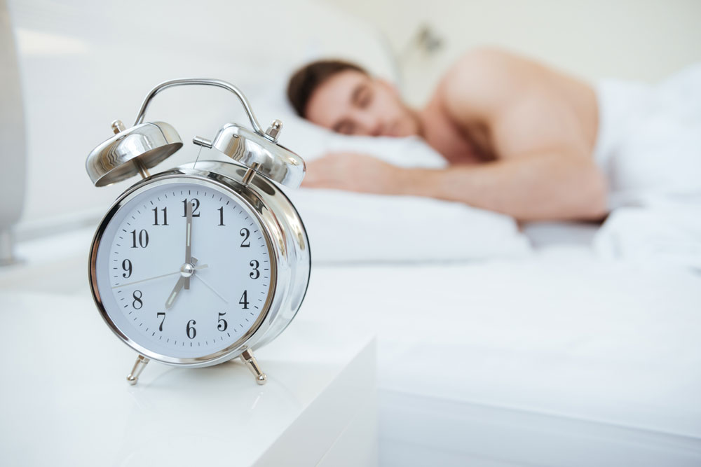 graphicstock-man-sleeping-on-bed-focus-on-clock-which-on-nightstand-near-the-bed_rds3B682e
