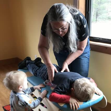 Dr. Kareen adjusting a little boy