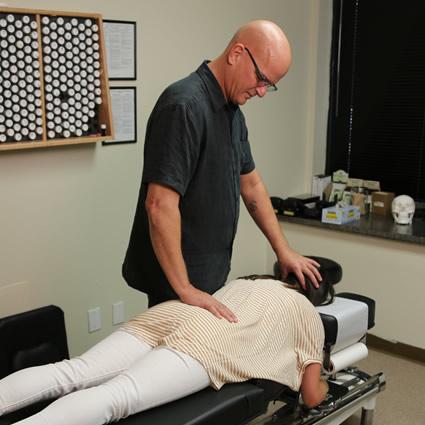 Dr. Apol adjusting woman's back