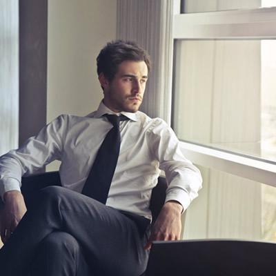 man sitting beside window looking outside