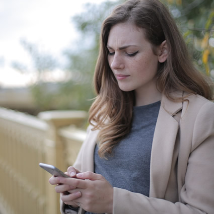 woman reading phone stressed