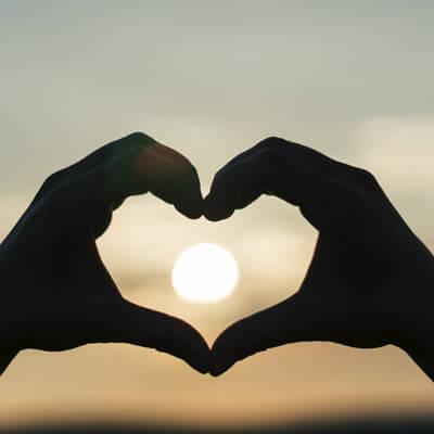hands making a heart shape against a sunset