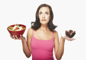 Woman deciding between a salad and piece of cake