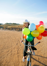 Woman riding a bike with balloons
