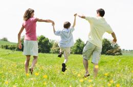 Family running through a grassy field