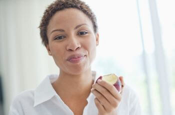 Woman chewing apple.