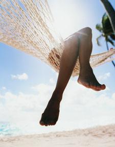 Woman lounging in sun in a hammock