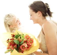 Daughter handing mother flowers