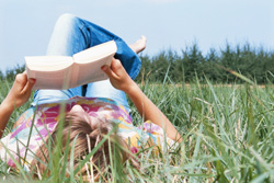 Woman reading a book in the grass