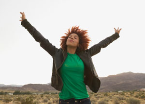 A women standing outside with her arms stretched out