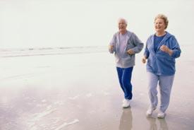 Seniors running on beach together