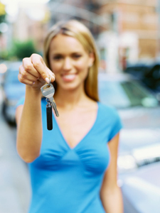 Young woman holding up a set of car keys