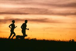 Man, woman and dog running at sunrise