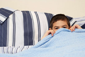 Boy hiding under his bed sheets