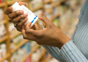 woman reading a supplement bottle label