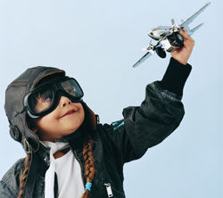 Young child in aviator outfit flying toy plane