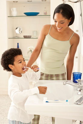 Mother helping son brush teeth