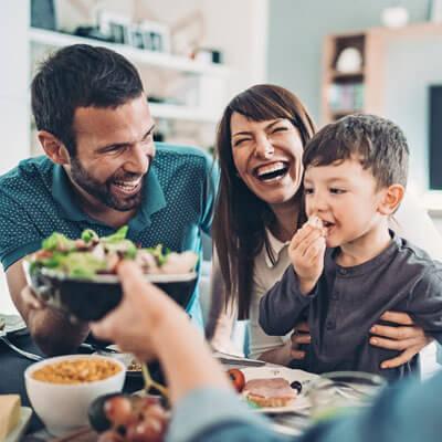 Family laughing eating dinner