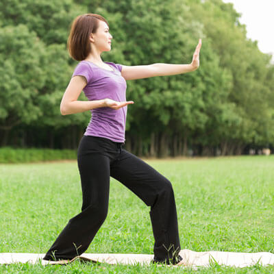 woman doing tai chi in the park