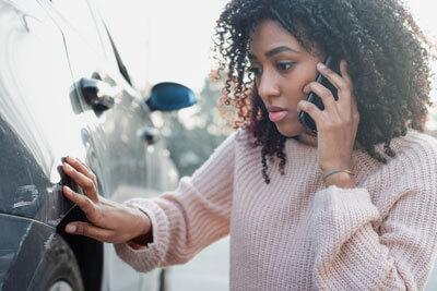 Woman looking at damaged car