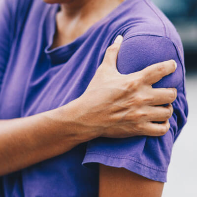 Adult holding shoulder in pain