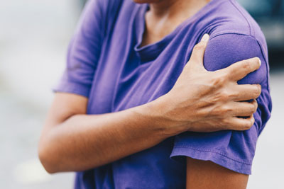 Young adult holding shoulder in pain